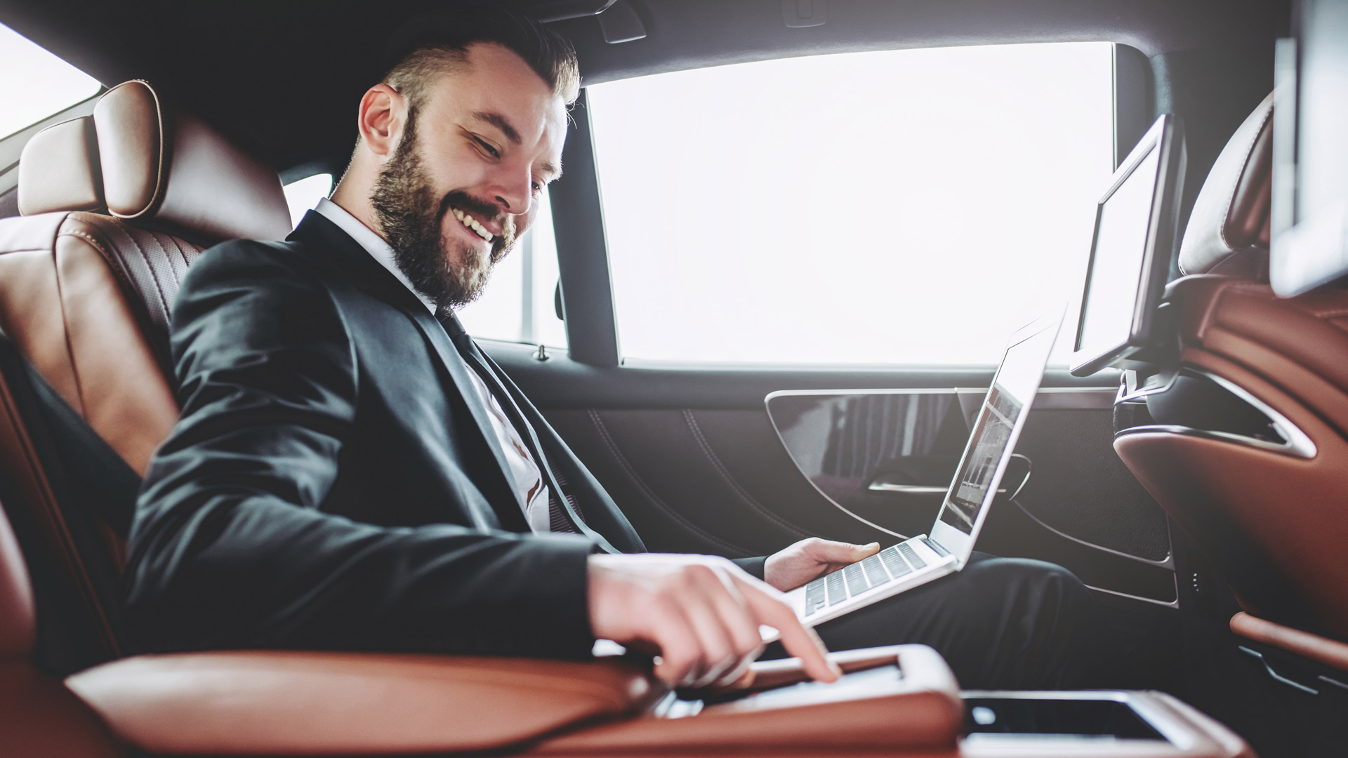Young handsome businessman is sitting in luxury car. Serious bearded man in suit is working with laptop while being in trip.
