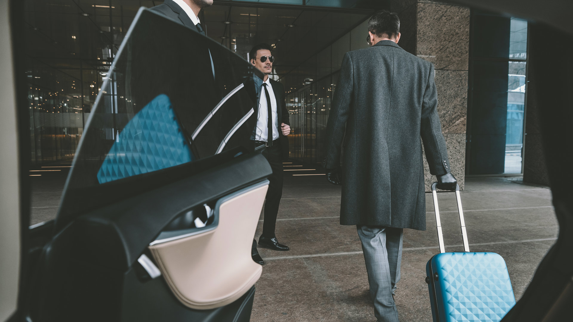 Businessman going with blue bag on wheels to airport